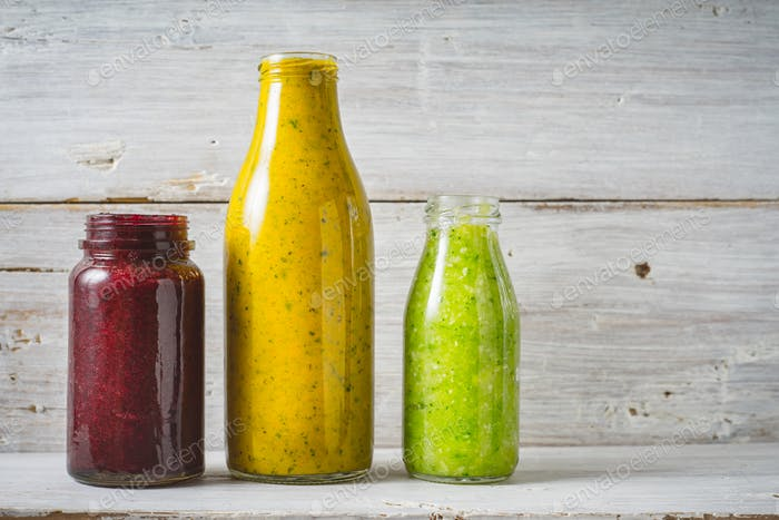 Green, yellow and red smoothie in the glass bottle on the white wooden background