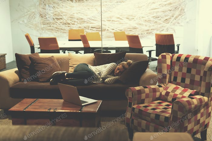 woman sleeping on a sofa  in a creative office