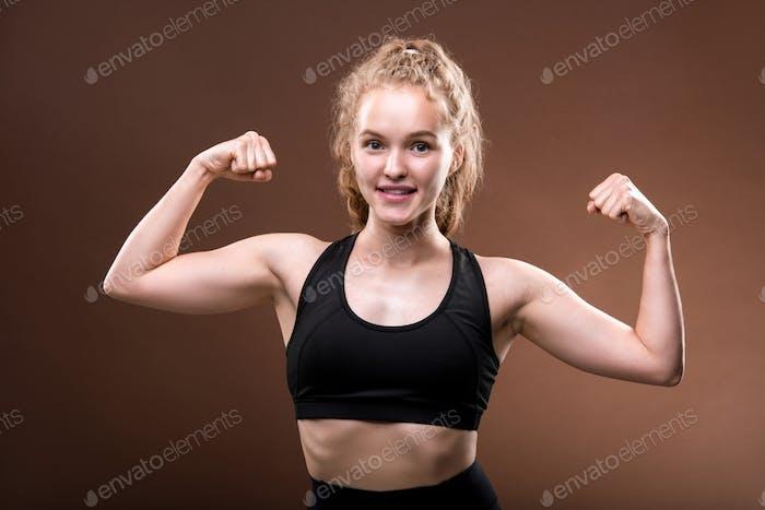 Junge weibliche Athlete im Trainingsanzug machen Geste zeigt ihre körperliche Kraft