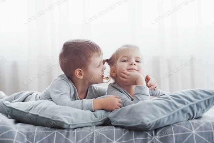 Kinder wachen im sonnigen weißen Schlafzimmer auf. Junge und Mädchen spielen in passenden Pyjama