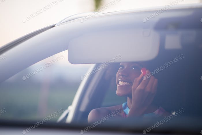 woman making makeup while driving car