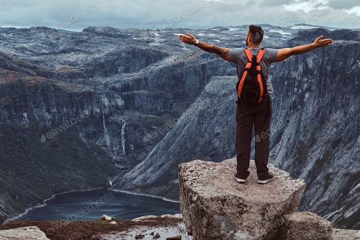 Tourist stands on the peak of the mountain with an amazing view of the Norwegian fjord.