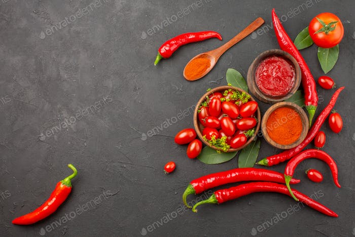 top view a bowl of cherry tomates hot red peppers a wooden spoon bay leaves bowls of ketchup and