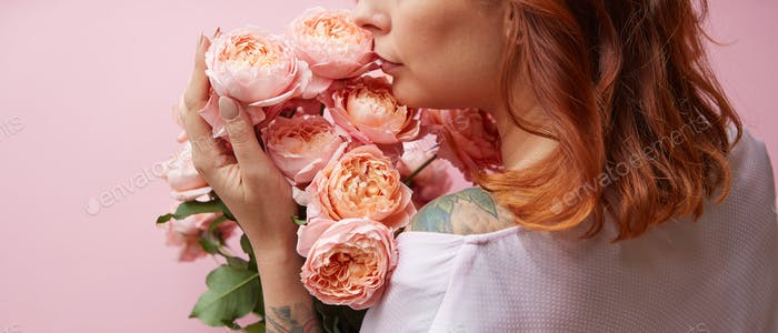 Red-haired woman with tattoo on her shoulders holds delicate fresh coral roses on a living coral