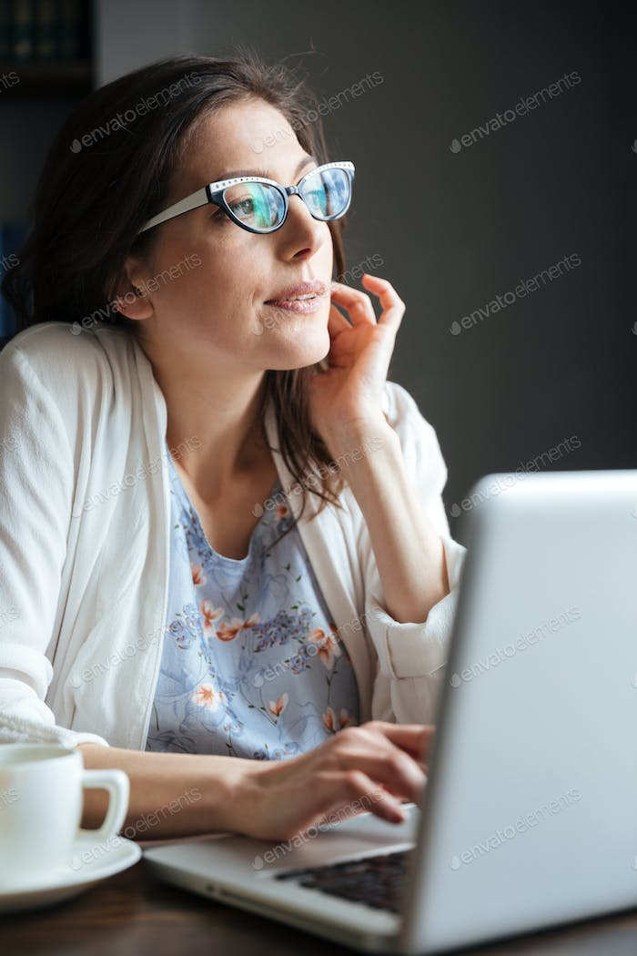 Portrait of a thoughtful mature woman typing on laptop