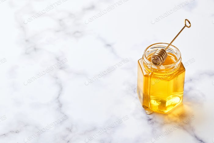 Glass jar with floral liquid honey and metal honey spoon on light marble background