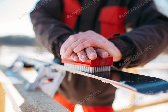 Skier prepares his skis for riding, winter sport
