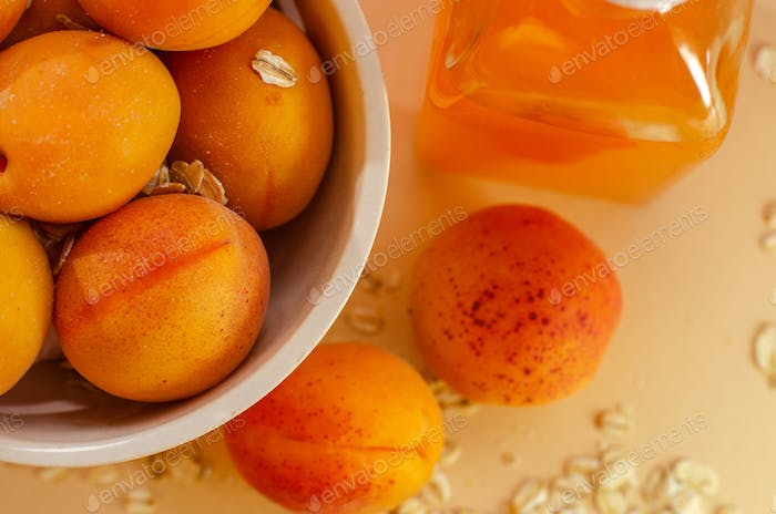 Lots of apricots on a white plate and glass of apricot juice on a white table strewn with oatmeal.