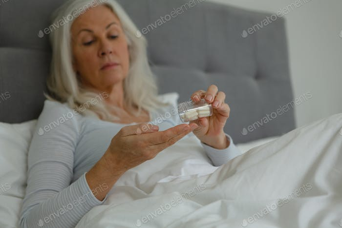 Front view of active senior Caucasian woman taking medicine in bedroom at home