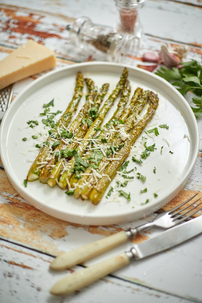 Roasted asparagus with parmesan cheese and parsley. Healthy spring food concept. View from above