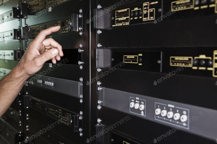 Close up of the hand of a technician working on a server in a large computer server room.