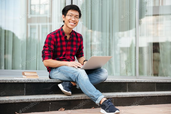 Happy asian young man using laptop outdoors