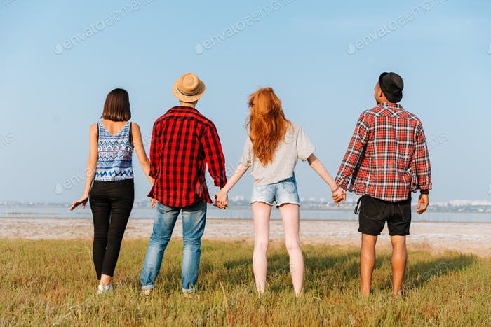 Back view of four happy young people holding hands outdoors
