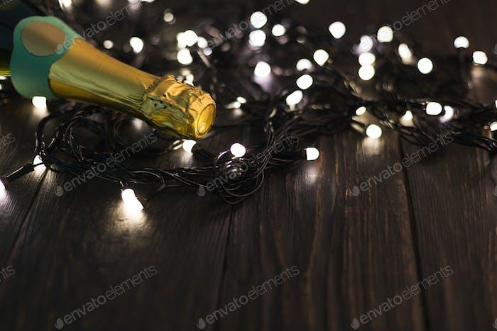 Champagnerflasche und Girlande auf dunklem Hintergrund