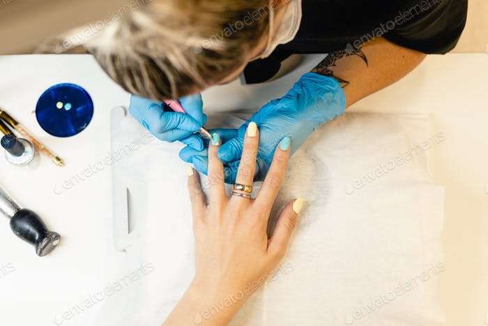 Close-up of Beautician painting her client's nails in blue and yellow nail varnish