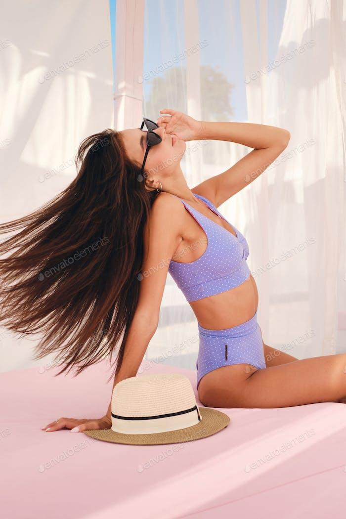 Hermosa chica morena con el pelo Largo en lindo traje de baño y gafas de sol descansando en la Playa cama