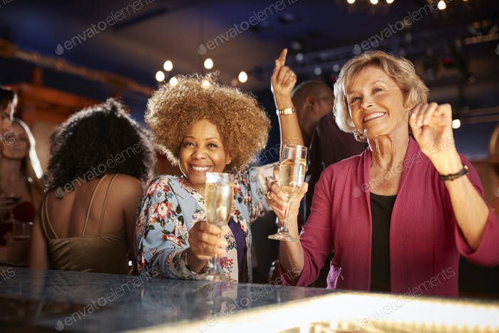 Portrait Of Female Senior Friends Drinking And Dancing In Bar Together