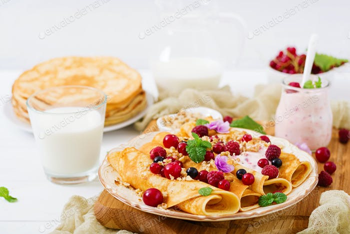 Pancakes with yoghurt, honey, nuts and summer berries. Tasty breakfast.