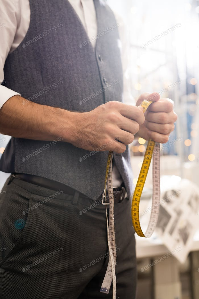 Tailor Holding Measuring Tape Close Up