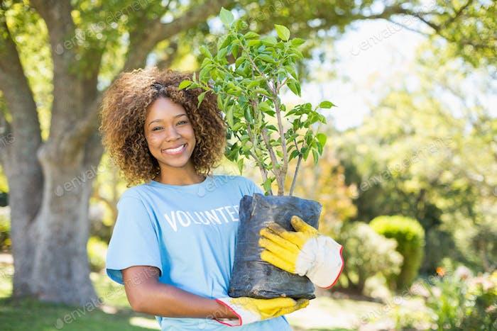 Portrait of volunteer woman holding plant