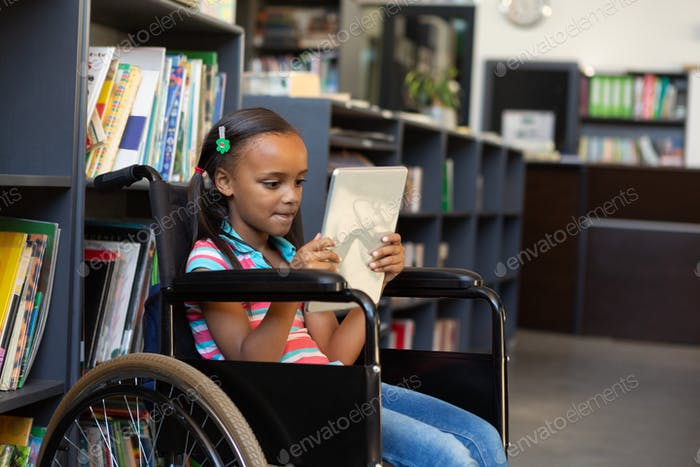 Side view of a disabled mixed-race schoolgirl using digital tablet in the library at school