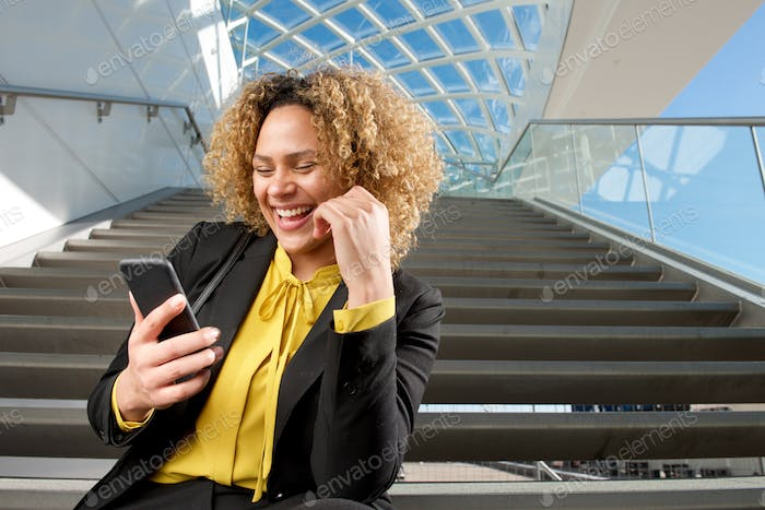 happy businesswoman sitting on stairs looking at mobile phone