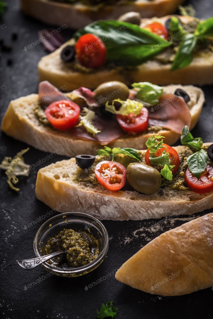 Slices of ciabatta with olives , tomatoes and basil on the black stone table vertical