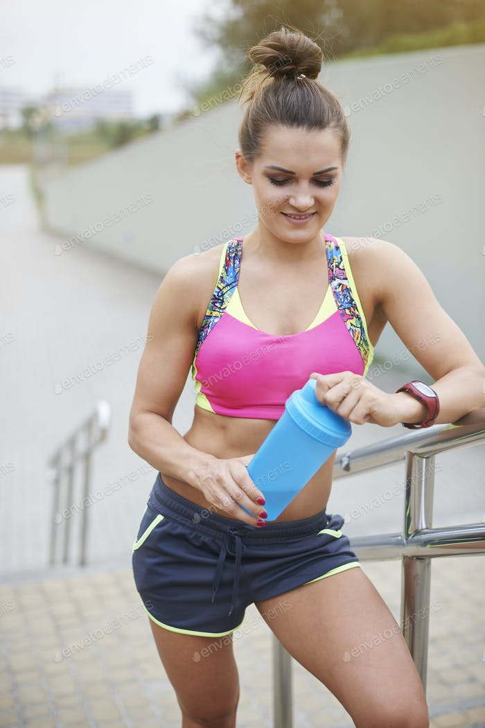 Sporty woman holding a bottle full of proteins