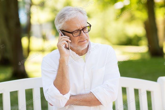 senior man calling on smartphone at summer park