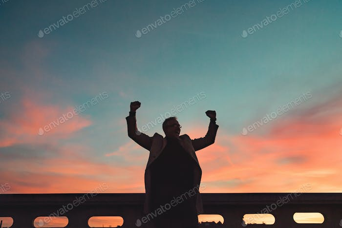 A silhouette of businessman standing on a bridge at dusk, expressing excitement.
