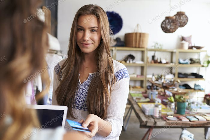 Teenage young woman paying with credit card in a boutique