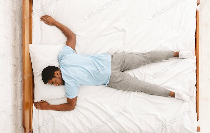 Young african-american man sleeping in bed top view