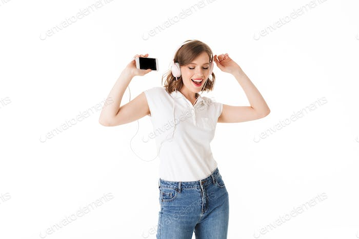 Portrait of beautiful lady in headphones happily dancing with cellphone in hand