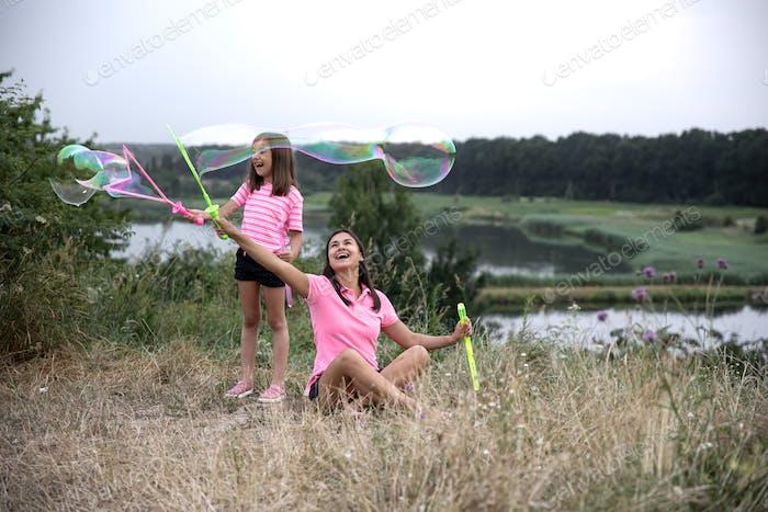 Little girl and mom are playing with big soap bubbles in nature.