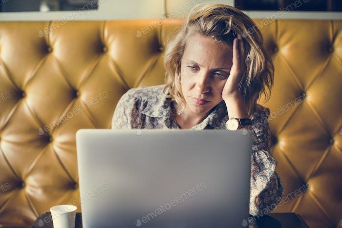 Blond Frau arbeitet an ihrem Laptop in einem Café