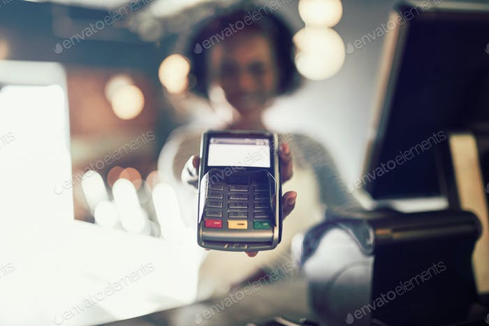 Restaurant waitress holding an electronic card payment machine