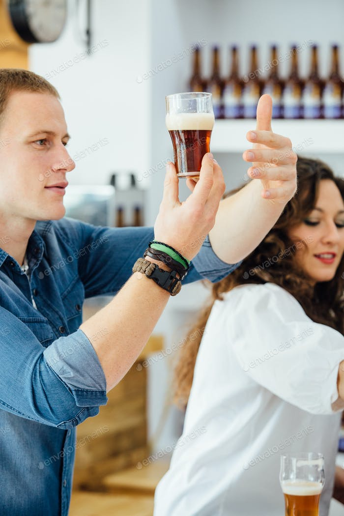 Man covering glass of beer with hand