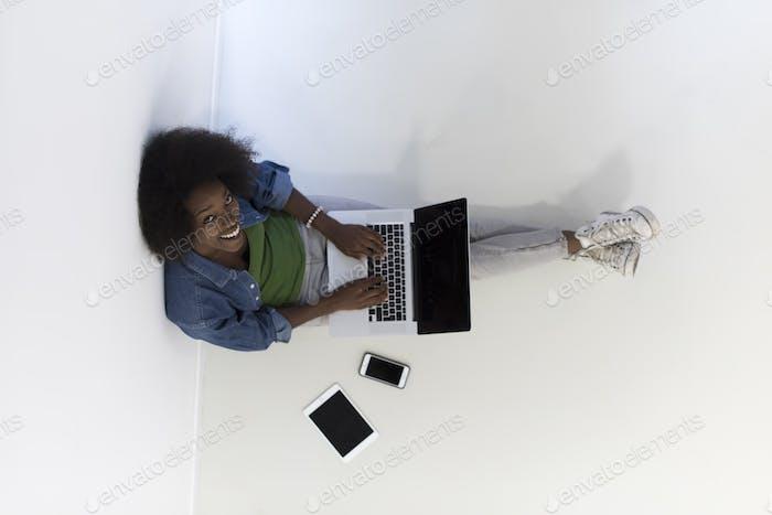 African American Frau sitzt auf dem Boden mit Laptop Draufsicht