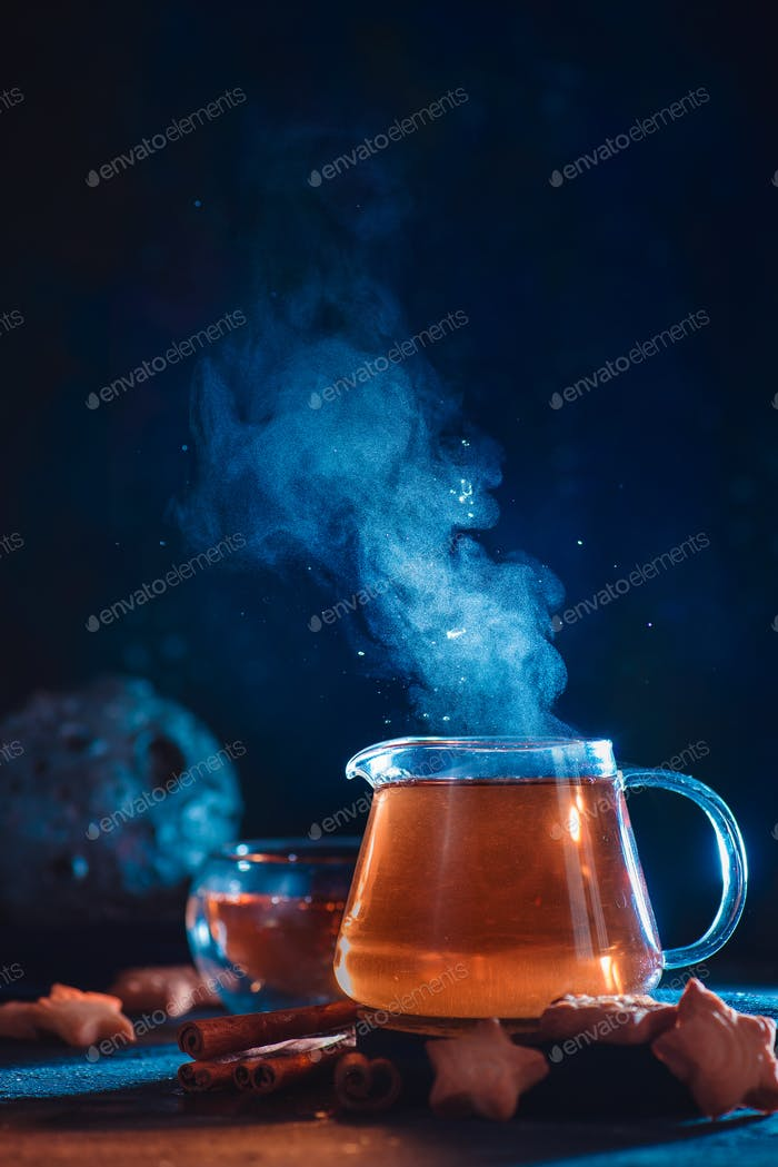 Glass teapot with rising steam and star-shaped cookies on a dark background with copy space