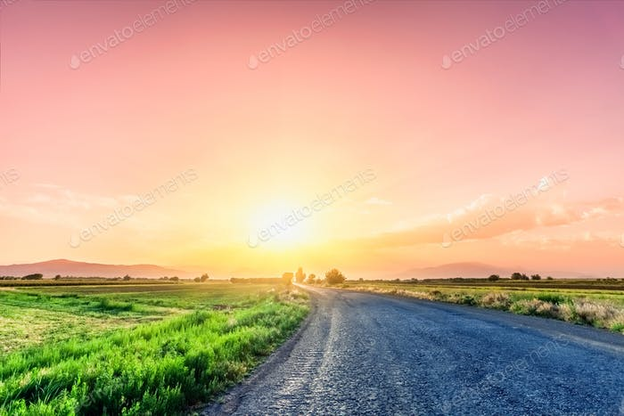 Road on meadow with beautiful sunset sky