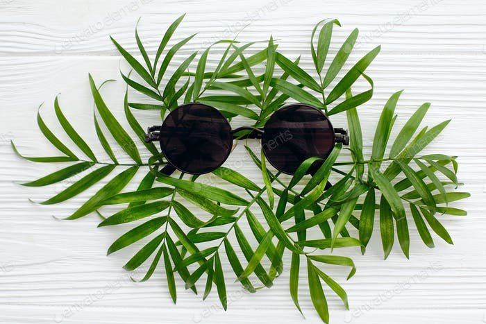 Stylish black sunglasses on green palm leaves on white wooden background