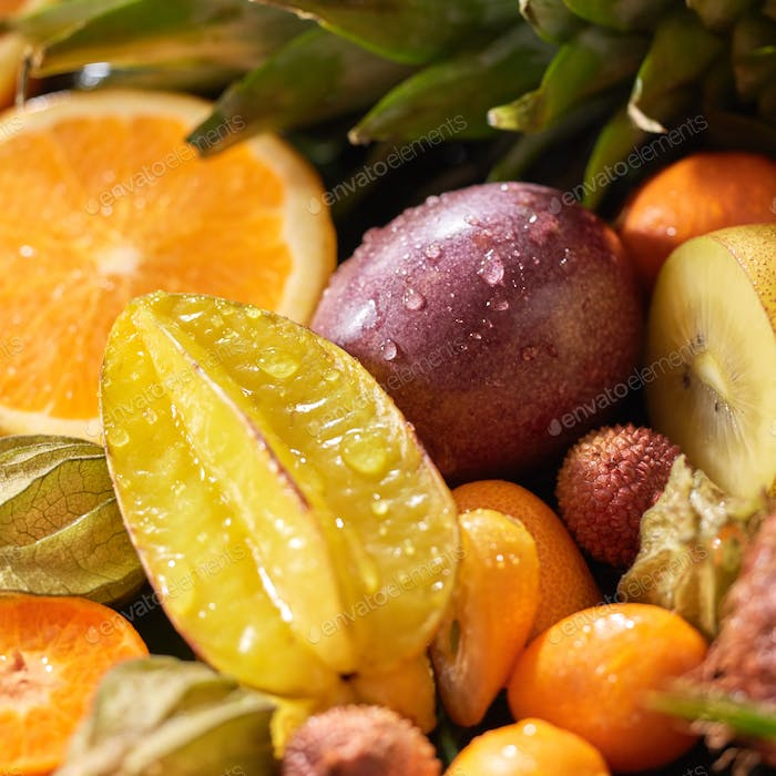 Close-up tropical background with fresh helthy fruits carambola, passion fruit, orange, kumquat