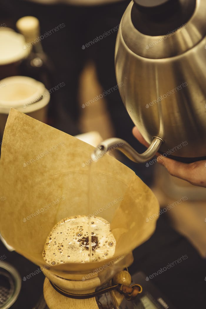 Barista pouring water to coffee