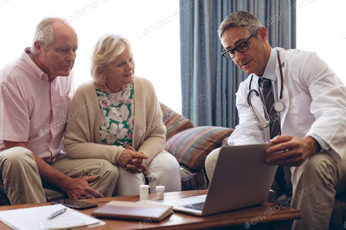 Confident male doctor discussing over laptop with senior Caucasian couple at retirement home