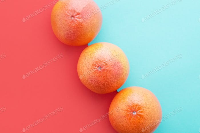 Grapefruits Diagonal on Coral and Blue Color Background, Minimal Summer Flat Lay.