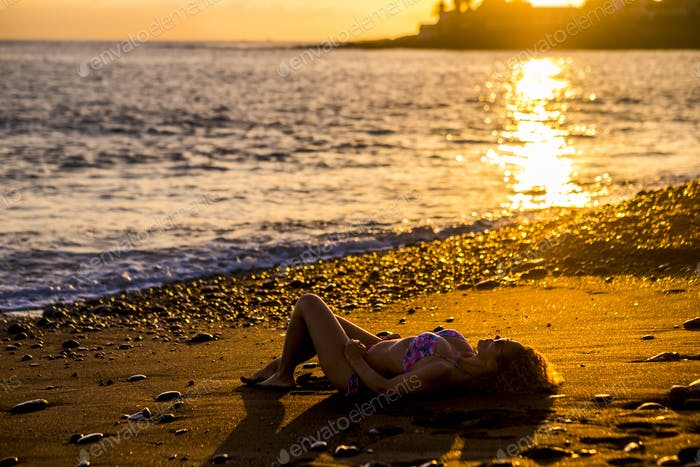 beautiful caucasian young woman take sun and relax at the beach during the sunset