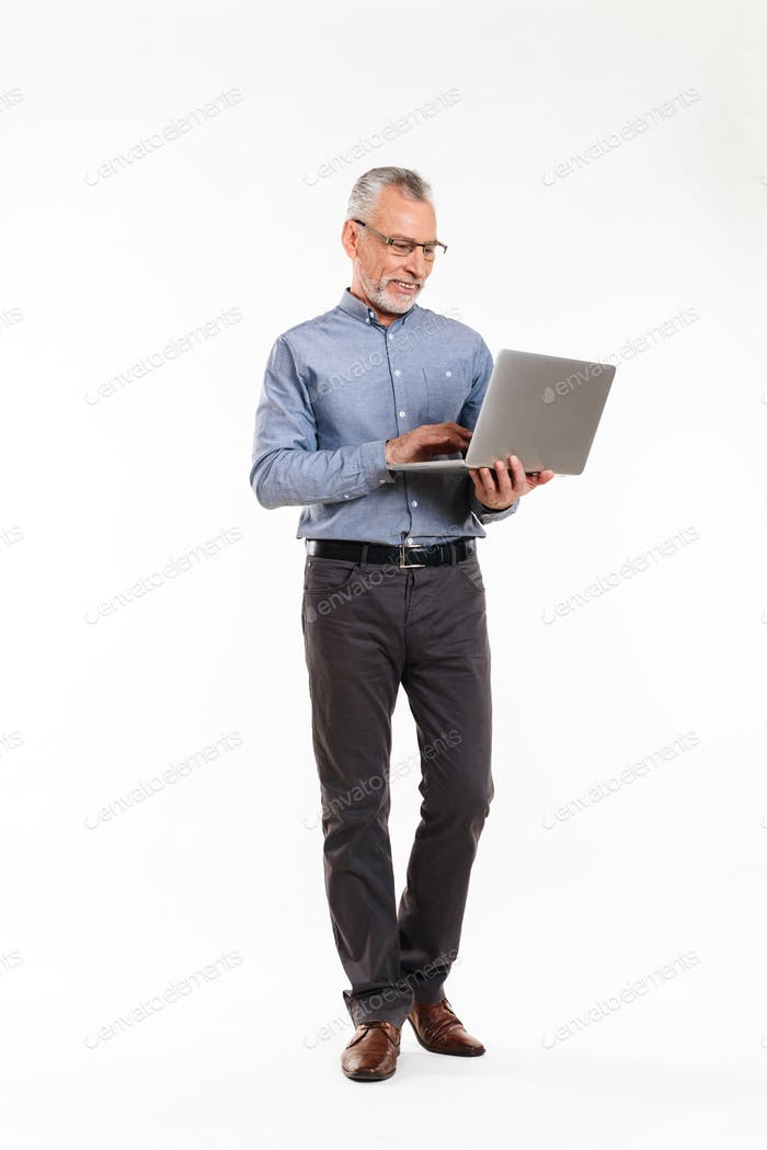 Cheerful mature man in eyeglasses using laptop computer