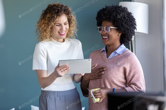 Two casual young business women working with the digital tablet in the new office.
