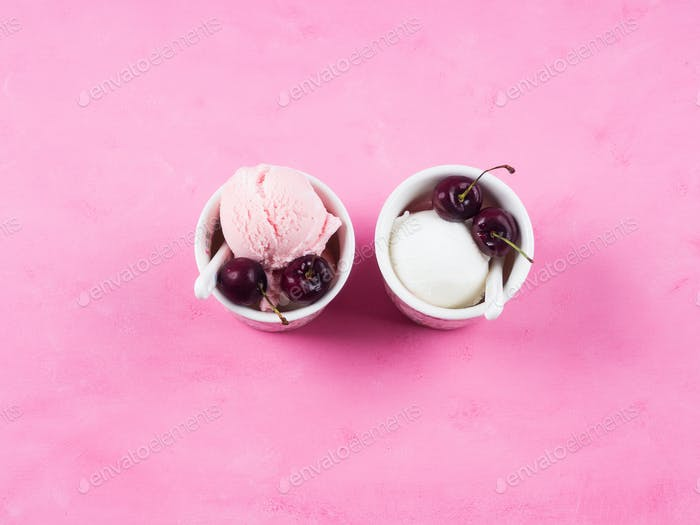 Two ice cream cups with cherries on pink