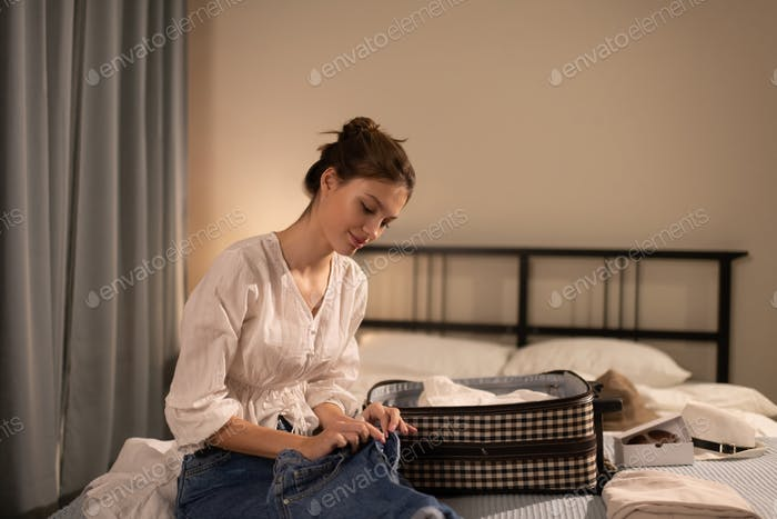 Glad woman packing clothes on bed